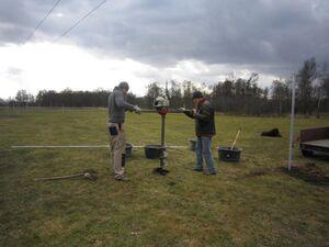 Zwei Männer bohren mit einem Erdbohrer ein Loch auf einer Wiese.