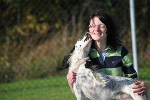 Eine junge Frau schmust Kopf an Kopf mit einem weiß-schwarzen Hund.
