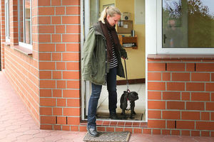 Ein Mensch geht mit einem kleinen Hund durch die Tür.