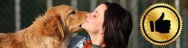 Eine dunkelhaarige Frau schmust mit einem hellen Hund.