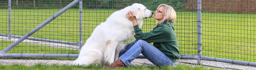 Eine junge Frau schmust liebevoll mit einem großen, weißen Hund.