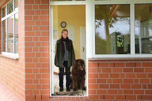 Mensch und Hund warten an einer geöffneten Tür.